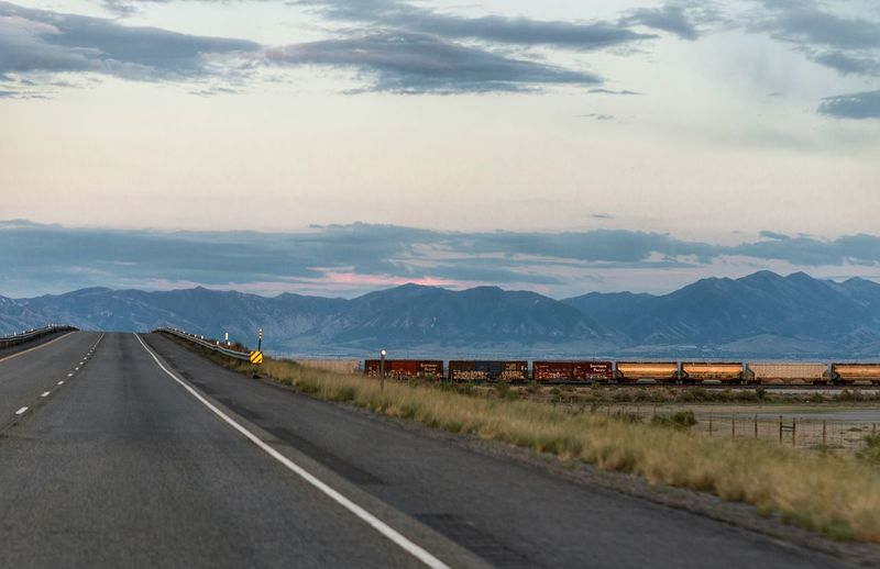 Freight locomotive moving through country road along landscape