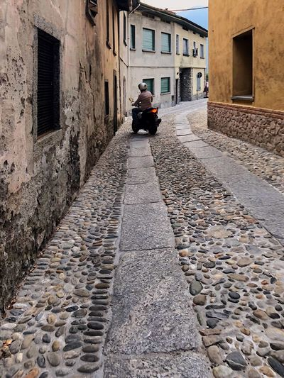 a man rides a moped through a small Italian street with old houses, paved with cobblestones. Traveling Travel Exterior Building Old Street Old Town Cobblestone Streets Cobblestone Building Exterior Built Structure Architecture Transportation Mode Of Transportation City Building Street Land Vehicle Residential District Motor Vehicle Direction The Way Forward Road Outdoors House