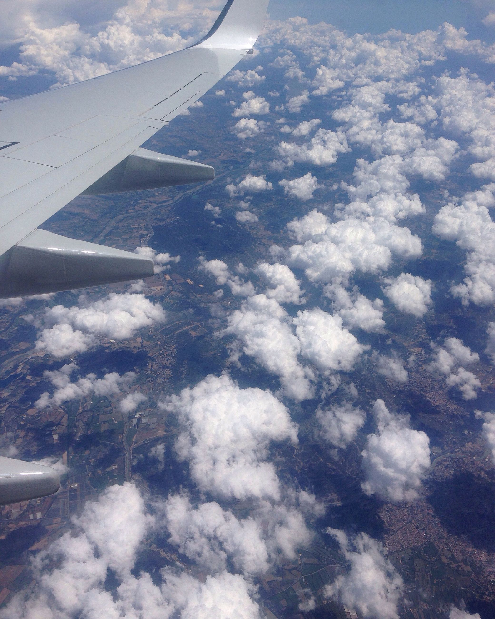 transportation, mode of transport, aircraft wing, flying, air vehicle, airplane, cropped, part of, aerial view, journey, travel, landscape, mid-air, scenics, mountain, on the move, aeroplane, cloud - sky, cloud, cloudscape, day, tranquil scene, nature, beauty in nature, sky, airplane wing, mountain range, sea, majestic, blue, snowcapped mountain, solitude, tranquility, non-urban scene, outdoors