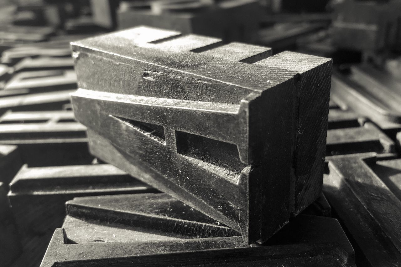 metal, no people, close-up, focus on foreground, pattern, indoors, day, girder
