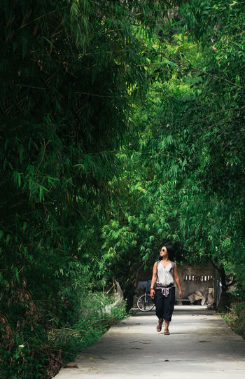 A young girl walks through a copse of trees in Vietnam. Alone ASIA Beauty In Nature Forest Full Length Girl Green Hanoi Lifestyles Looking Up Natural Nature One Person Outdoors Path Portrait Solo Sunlight Travel Trees Vietnam Walking Woman Woods