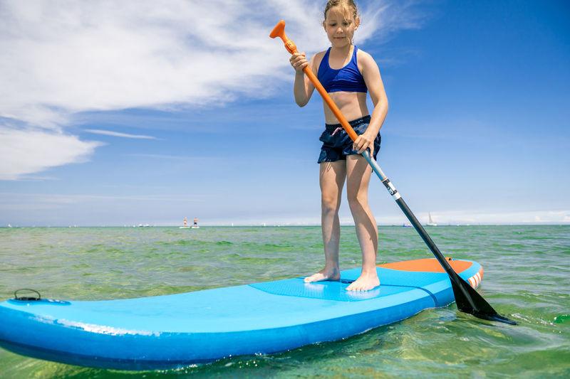 Boy on sea shore against sky
