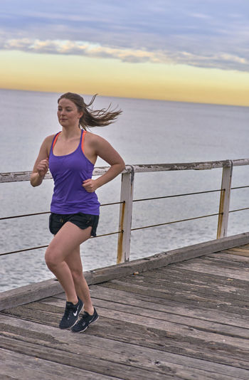 Young Woman Running On Pier Against Sky During Sunrise