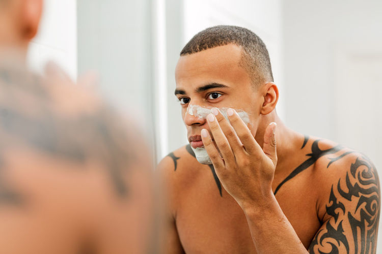 Tattooed shirtless man applying shaving cream on face while looking in mirror