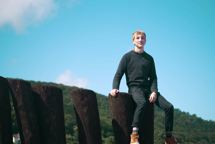 Portrait of young man sitting on wooden logs against sky