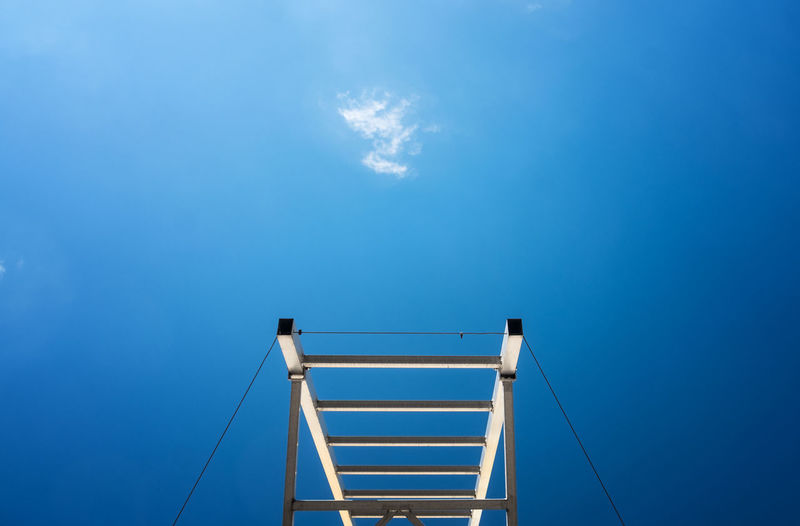 Low angle view of ladder against blue sky