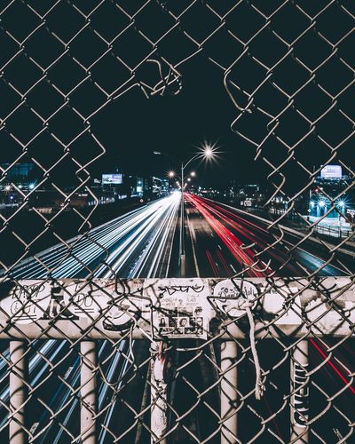 Light trails on bridge against sky in city at night