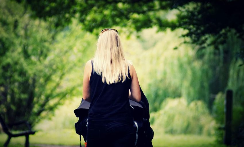 Rear view of woman with blond hair standing against trees in park