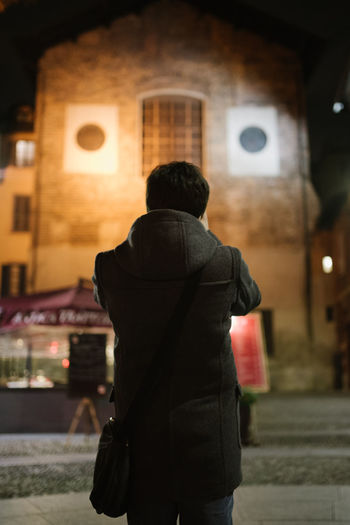 Rear View Of Man Standing In Front Of Church At Night