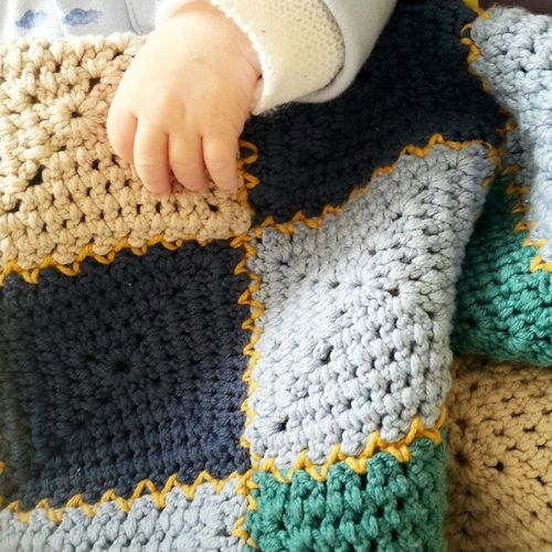 Cropped hand of baby holding knitted fabric