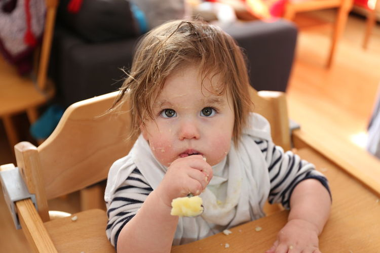 Close-up of cute baby girl with messy face looking away while sitting on chair at home