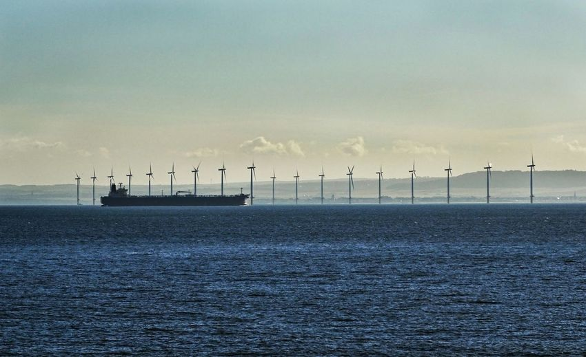 Container Ship Sailing In Sea By Windmills Against Sky