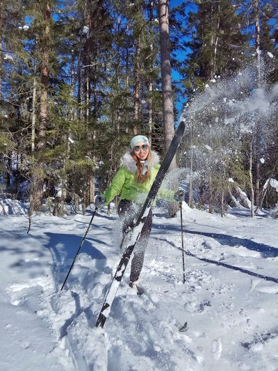 Portrait of young woman skiing against trees against forest