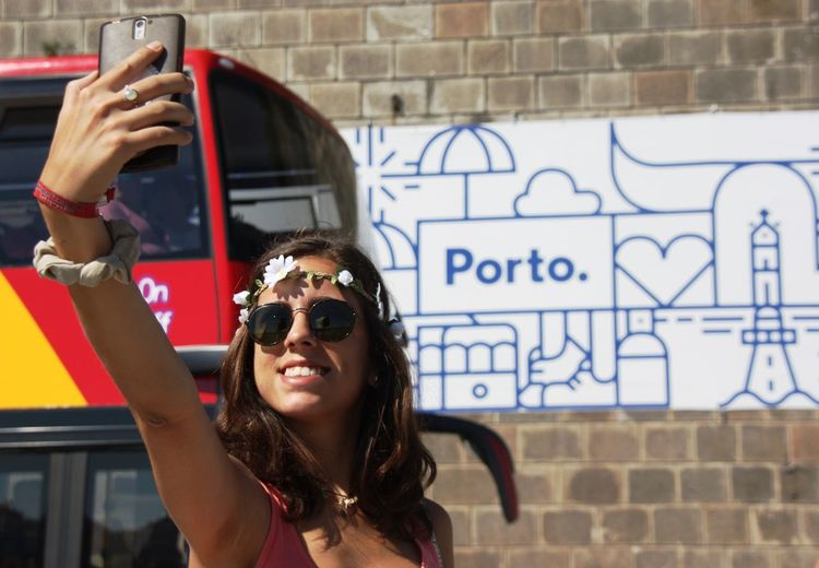 Young woman clicking selfie through mobile phone by bus