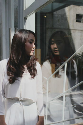Young Woman Wearing White Dress Looking Through Window In City