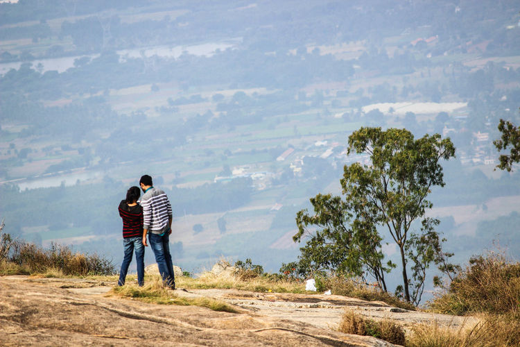 Rear View Of Couple Standing On Mountain