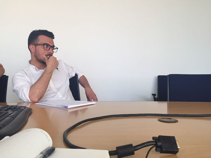 Serious man sitting at conference table against wall in office meeting