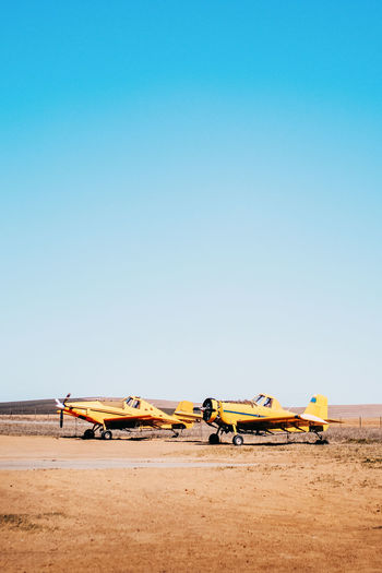 Airplanes on sand in desert against clear blue sky