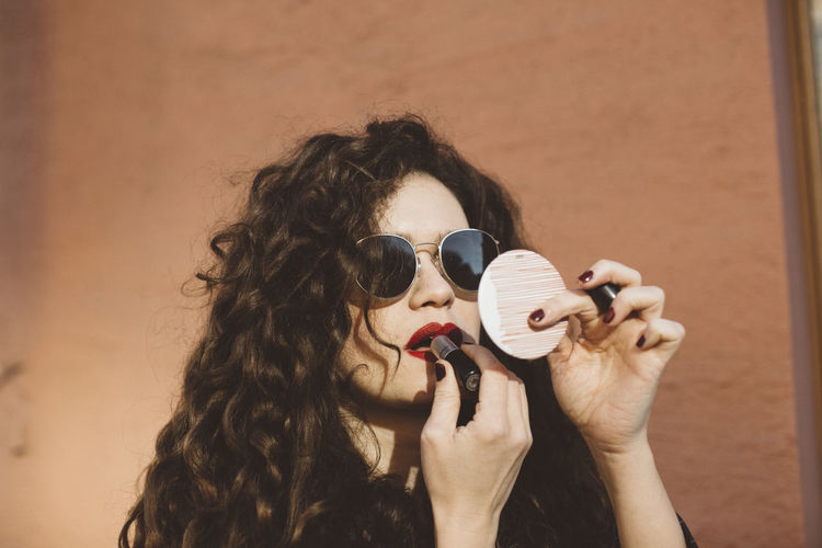 Portrait of woman holding sunglasses outdoors