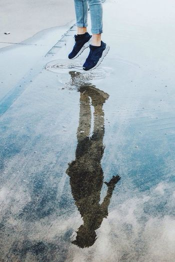 Low section of man jumping on puddle