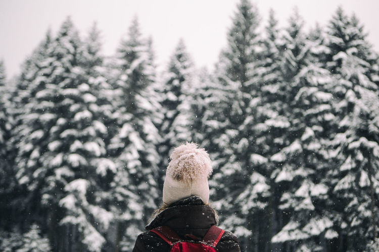Close-Up Of Person Standing By Tree Against Sky During Winter
