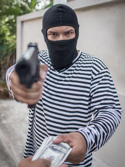 Portrait of burglar aiming handgun outdoors