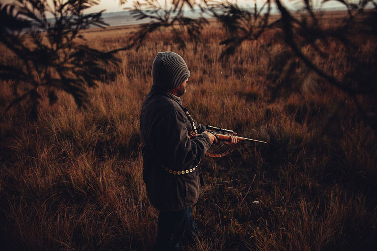 Hunter With Shotgun Standing In Field During Sunrise