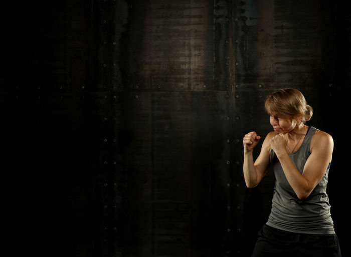 Athlete standing in fighting stance against wall