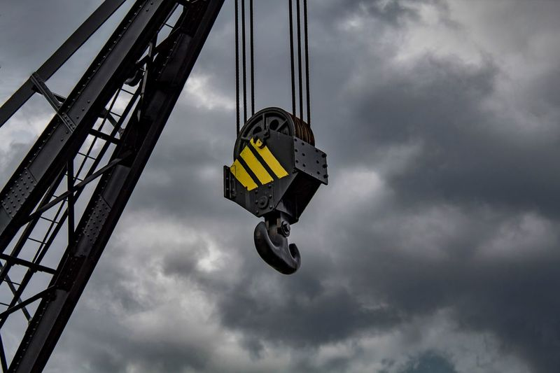 Low angle view of hook hanging on crane against cloudy sky