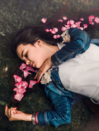 High angle view of woman with rose petals on hair lying over grass