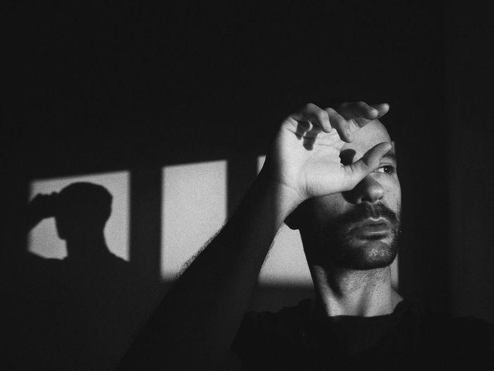 Man looking away while sitting in darkroom
