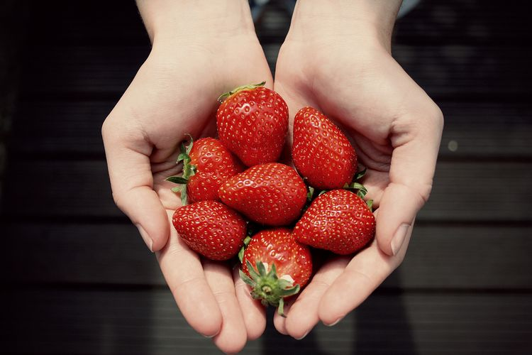 Cropped hands showing strawberries at home