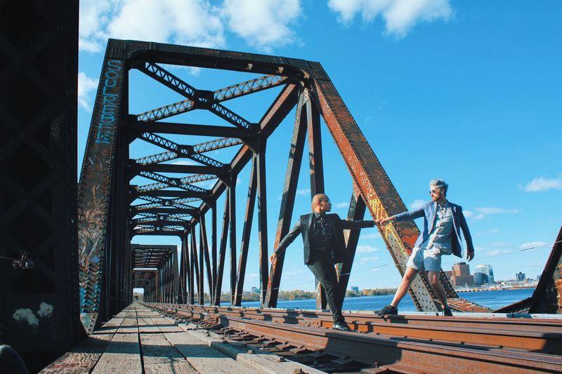 People standing on bridge against sky