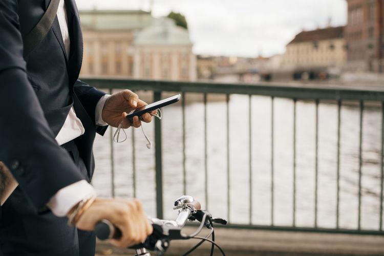 Man holding bicycle on railing