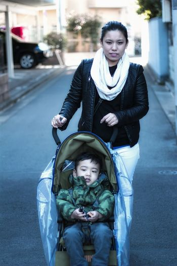 Portrait Of Mother Pushing Baby Carriage On Street