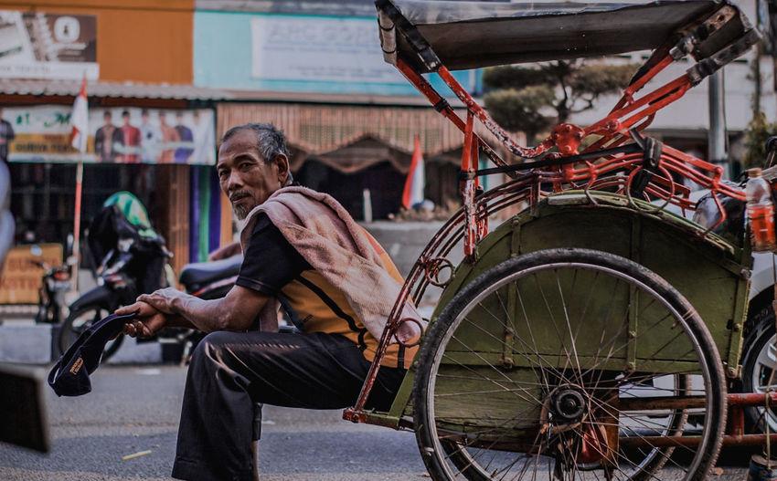 Side View Of Senior Man Sitting In Jinrikisha On Street