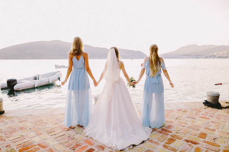Rear view of bride holding hands with bridesmaids by sea against clear sky