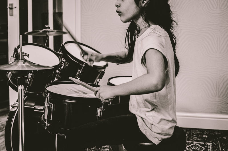 Midsection of girl playing drum at home