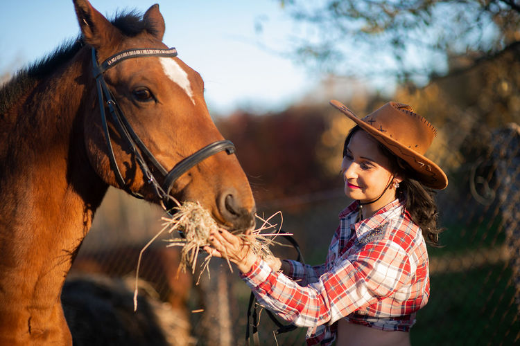 Horse Farm Horse Breed Horse Breeds Brown Girl Cowboy Cowboy Hat Cowboygirl Woman Female Horse Feeding Feeding  Hay Human And Animals Animals And Humans Domestic Animals Sunlight Horse Head Lifestyle