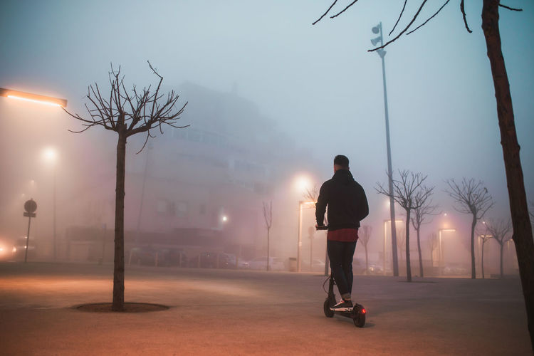 Rear view of man standing on street against sky during foggy weather