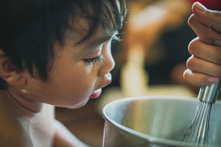 Baby boy looking at cropped hand preparing food
