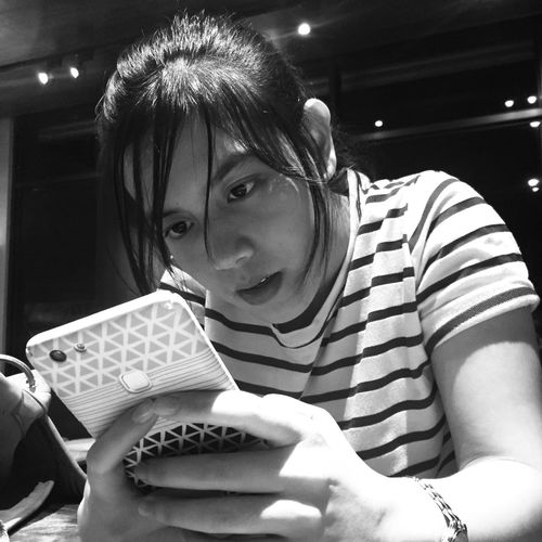 Close-up of young woman using phone while sitting at table