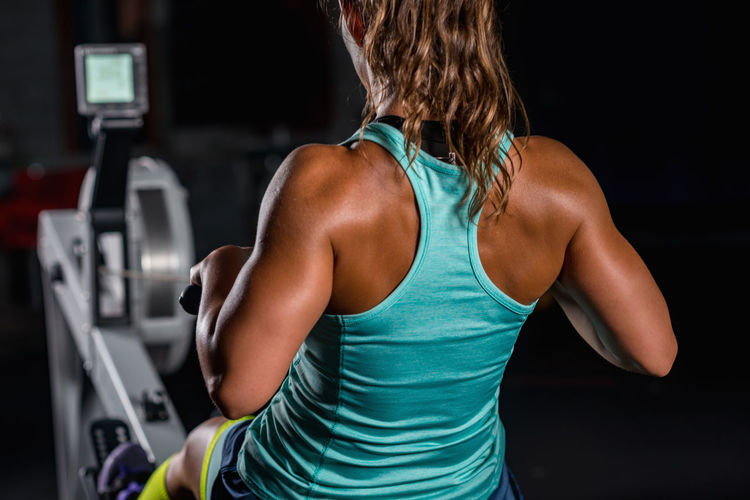 Rear View Of Mid Adult Woman Exercising In Gym