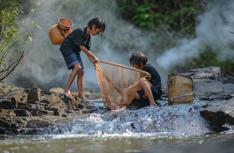 Full length of sisters with fishing net in river at forest