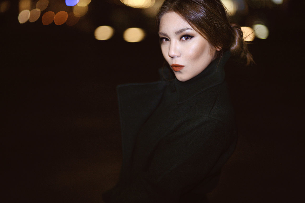 Portrait of beautiful young woman standing outdoors at night