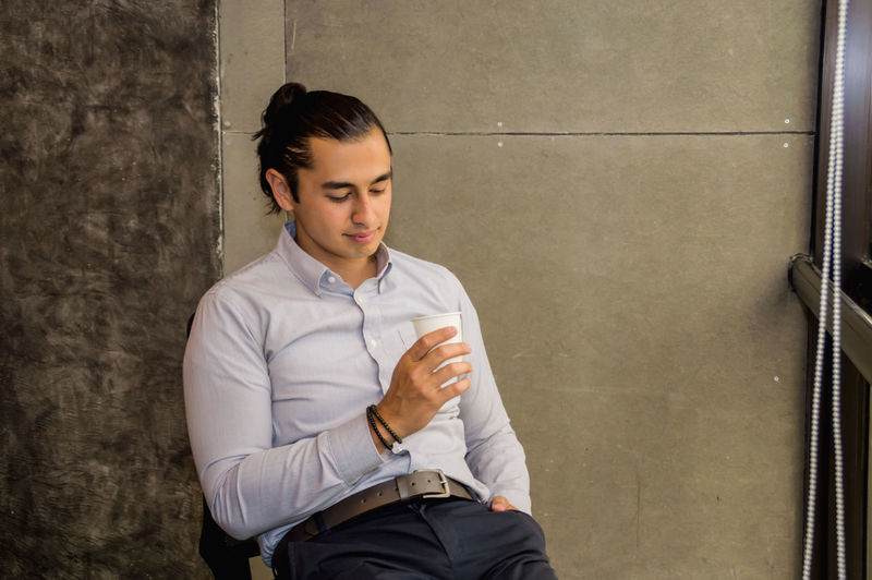 Young are relaxing at work in the office. Adult American Apartment Aroma Attractive Background Banner Beautiful Break Business Cafe Call Calm Care Carefree Casual Caucasian Chair Coffee Cup Cute Drink European  Happy Indoor Lifestyle Look Male Man Mobile Office People person Portrait Relaxing Resting Room See Sit Smart Smile Sunset Tasting Tea Tranquil White Window Wood Work Young