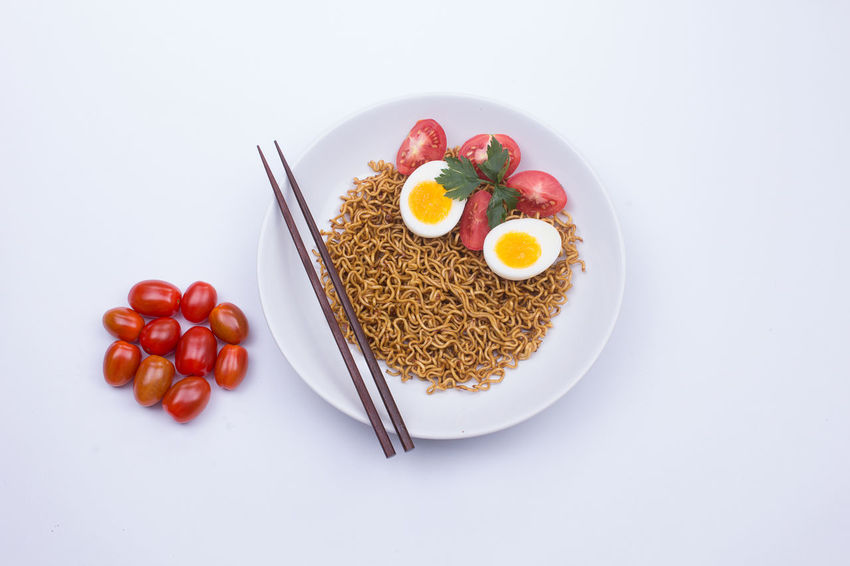 Fried noodle on a white plate styled beautifully Fried Noodles Noodles Boiled Egg Breakfast Egg Food Food And Drink Freshness Healthy Eating High Angle View Indoors  Meal No People Noodle Plate Ready-to-eat Still Life Studio Shot Temptation Tomato Vegetable Wellbeing White Background