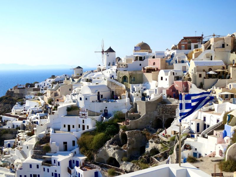 Architecture Blue Elevated View Flag Greece Houses Landscape Nature No People Oia Outdoors Residential District Santorini Sky Sunny Day The Essense Of Summer Town TOWNSCAPE Volcanic Island