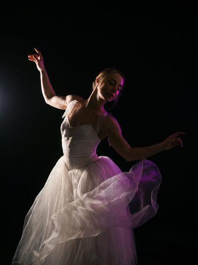 Ballet Dancer Wearing White Dress Dancing Against Black Background