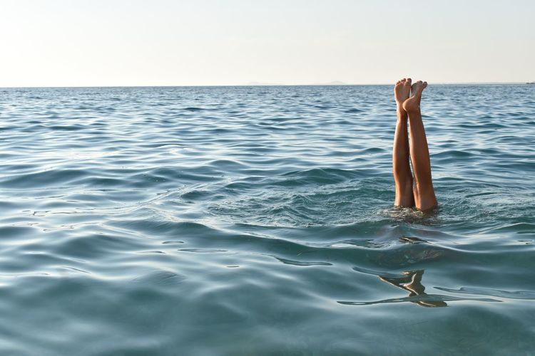 Low section of woman swimming in sea against clear sky during sunset